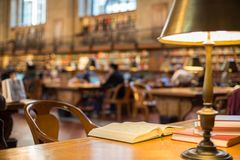 Book on wooden table in reading room in library Royalty Free Stock Photos