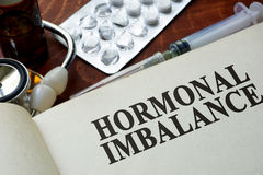 Book with words hormonal imbalance. On a table stock images