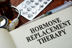 Book with words hormone replacement therapy. On a table royalty free stock photography
