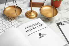 Book with words PERSONAL INJURY LAW. And scales of justice on table, closeup royalty free stock photo