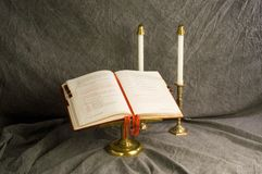 Book of Worship. A service book on stand with candles royalty free stock photo