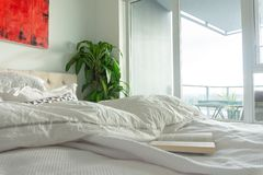 Book on wrinkled, used bed in a bright apartment bedroom with tall windows and window light. Depicting a royalty free stock image