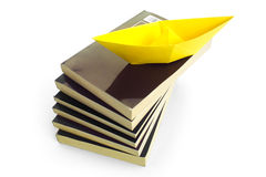 WITH A BOOK YOU CAN TRAVEL 2. An origami boat shipping over the books Stock Images