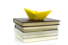 WITH A BOOK YOU CAN TRAVEL 1. An origami boat shipping over the books Royalty Free Stock Image