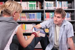 That is book You need. Woman giving a book to the man in the library Stock Photos