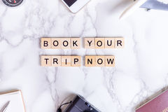 Book your trip now invitation poster with text and luxury travel accesories Royalty Free Stock Image