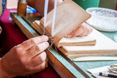 Bookbinding. Male worker binding pages. stock images