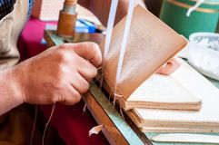 Bookbinding. Male worker binding pages. stock photography