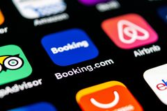 booking ícone da aplicação de COM no close-up da tela do iPhone X de Apple Ícone do app do registro booking com Meios sociais app imagem de stock royalty free