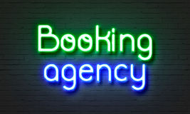 Booking agency neon sign on brick wall background. Stock Photos