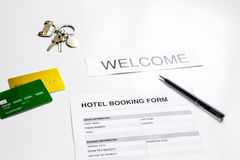 Booking hotel room application form and keys white desk background Royalty Free Stock Photo