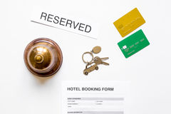 Booking hotel room application form and keys white desk background top view Royalty Free Stock Photo