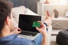 Booking tickets online for vacation. Booking tickets online on laptop and credit card. Unrecognizable man preparing for vacation, holding device with blank Stock Photo