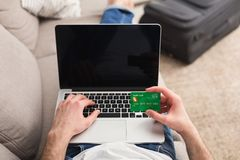 Booking tickets online for vacation. Booking tickets online on laptop and credit card. Unrecognizable man preparing for vacation, holding device with blank Stock Photography