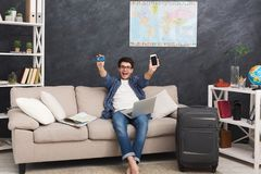 Booking tickets online for vacation. Booking tickets online on laptop, holding blank smartphone and credit card. Happy man preparing for vacation, paid for tour Stock Photo