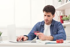 Booking tickets online for vacation. Booking tickets online on laptop and holding credit card. Concentrated young man preparing for vacation, travel and modern Royalty Free Stock Photography