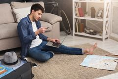 Booking tickets online for vacation. Booking tickets online on laptop and holding credit card. Concentrated young man preparing for vacation, travel and modern Royalty Free Stock Photo