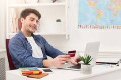 Booking tickets online for vacation. Booking tickets online on laptop and holding credit card. Happy man preparing for vacation, travel and modern technologies Stock Photos