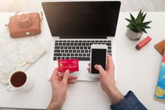 Booking tickets online for vacation. Booking tickets online on laptop and smartphone, holding credit card. Unrecognizable man preparing for vacation, holding Royalty Free Stock Image