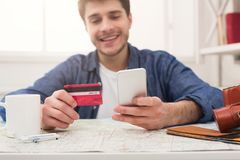 Booking tickets online for vacation. Booking tickets online on smartphone and holding credit card. Happy man preparing for vacation, travel and modern Royalty Free Stock Photography