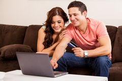 Booking a trip online. Happy young couple booking a vacation trip online together with a laptop computer and a credit card stock photos