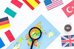 Booking trip with map, flags and tourist outfit on white office desk background top view stock photography