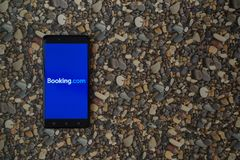 bookishly com-logo på smartphonen på bakgrund av små stenar royaltyfri bild