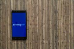 bookishly com-logo på smartphoneskärmen på träbakgrund royaltyfria bilder