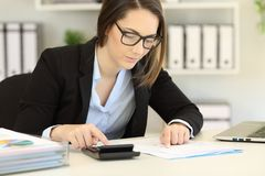 Bookkeeper calculating using a calculator. Serious bookkeeper calculating expenses using a calculator Royalty Free Stock Image