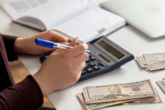 Bookkeeper counts money on calculator at the table. Horizontal photo of bookkeeper counts money on calculator at the table royalty free stock photo