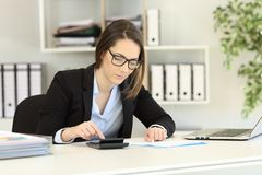 Bookkeeper doing accounting at office. Concentrated bookkeeper doing accounting at office Royalty Free Stock Images