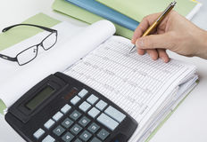 Bookkeeper or financial inspector making report, calculating or checking balance. Audit concept. Bookkeeper or financial inspector making report, calculating or royalty free stock photos