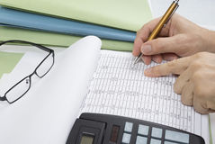 Bookkeeper or financial inspector making report, calculating or checking balance. Audit concept. Bookkeeper or financial inspector making report, calculating or stock photography