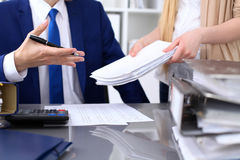 Bookkeeper or financial inspector and secretary making report, calculating or checking balance. Internal Revenue Service. Inspector checking financial document Stock Photo