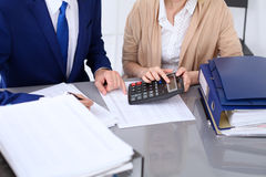 Bookkeeper or financial inspector and secretary making report, calculating or checking balance. Internal Revenue Service Royalty Free Stock Image