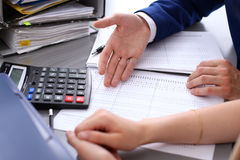 Bookkeeper or financial inspector and secretary making report, calculating or checking balance. Internal Revenue Service. Inspector checking financial document royalty free stock images