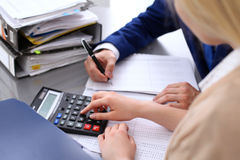 Bookkeeper or financial inspector and secretary making report, calculating or checking balance. Internal Revenue Service. Inspector checking financial document Royalty Free Stock Photos