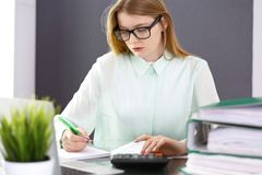 Bookkeeper or financial inspector woman making report, calculating or checking balance. Audit and tax service concept. Green colored image background stock images