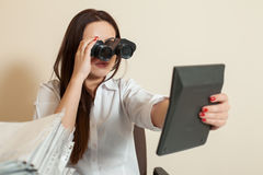 Bookkeeper looks through binoculars on calculator Royalty Free Stock Photo