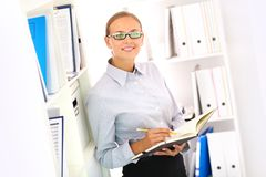 Bookkeeper. Portrait of a smiling bookkeeper standing by the shelves stock photos
