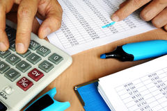 Bookkeeper using calculator to check the figures on the business report. Accounting and audit concept Stock Photo
