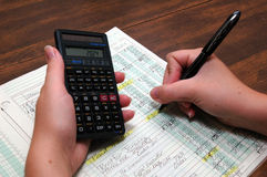 Bookkeeping. Entering figures on balance sheet.  Using calculator Stock Photography