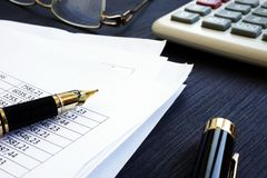 Bookkeeping. Financial report with figures and calculator on a desk. Bookkeeping. Financial report with figures and calculator on the desk stock image