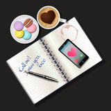 Booklet and mobile phone with cappuccino and macaroons Stock Photo