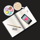 Booklet and mobile phone with latte and macaroons Royalty Free Stock Images