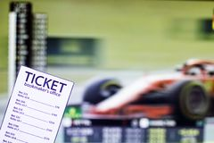 Bookmaker ticket on the background of the TV on which show the sports races the formula, sports betting, bookmaker stock photos