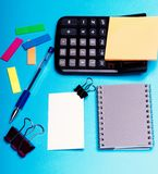 Bookmarks near grey notebook with pen on cyan background. Business card with empty space and binders near sticky notes. Stationery and calculator. Office royalty free stock image