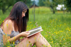 Bookreader. Young woman reading a book outdoors Stock Photo