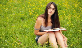 Bookreader. Young woman reading a book outdoors Royalty Free Stock Photography