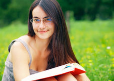 Bookreader. Young woman reading a book outdoors Royalty Free Stock Photo